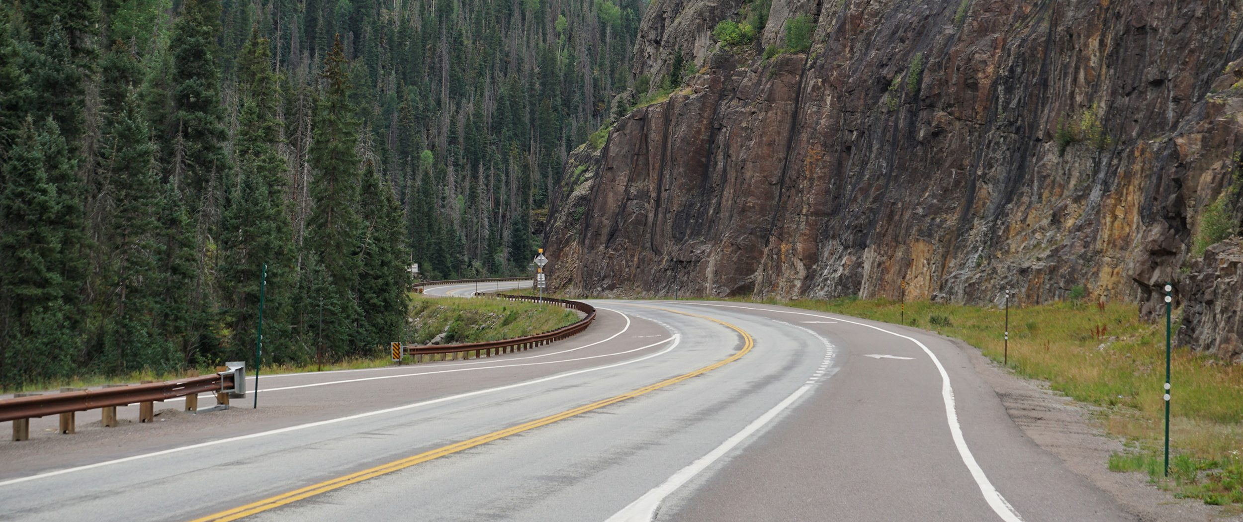 Winding highway with rocky cliff on one side, evergreen trees on the other